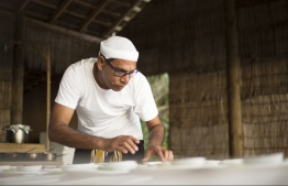 Chef de Cuisine at Soneva Fushi Abdulla Sobah preparing a dish in traditional Maldivian attire. PHOTO: SONEVA FUSHI