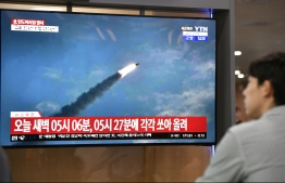A man watches a television news screen showing file footage of a North Korean missile launch, at a railway station in Seoul on July 31, 2019. - Pyongyang fired two ballistic missiles on July 31, Seoul said, days after a similar launch that the nuclear-armed North described as a warning to the South over planned joint military drills with the United States. (Photo by Jung Yeon-je / AFP)