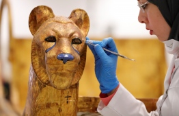 An Egyptian archaeologist restores the throne of the throne of King Tutankhamun at the conservation center in the Grand Egyptian Museum on August 4, 2019. - For the first time since the tomb was discovered in 1922, the coffin was transported from King Tutankhamun's tomb at the Valley of the Kings in Luxor to the Grand Egyptian Museum for an eight-month restoration process, before being displayed among his treasured collection at the museum. Tutankhamun is the formal name of the mummified pharaoh most tourists visiting Egypt's Valley of the Kings know as King Tut. (Photo by Khaled DESOUKI / AFP)