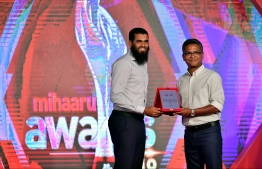 Executive Director of Mihaaru Vaail Zahir Hussain presents the special recognition award to