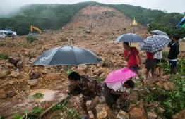 People watch rescue efforts after a landslide in Paung township, Mon state on August 10, 2019. - At least 22 people were killed and dozens injured when a landslide triggered by heavy monsoon rains struck a village in eastern Myanmar, as emergency workers continued the search on August 10 for the many feared missing. (Photo by Sai Aung MAIN / AFP)