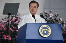 """South Korean President Moon Jae-in delivers a speech during a ceremony to mark the 74th anniversary of Korea's liberation from Japan's 1910-45 rule, at the Independence Hall of Korea in Cheonan on August 15, 2019. - South Korean President Moon Jae-in struck a conciliatory tone towards Japan on August 15, offering to """"join hands"""" if Tokyo chooses dialogue as relations between the two dip to fresh lows. (Photo by Jung Yeon-je / POOL / AFP)"""