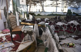 Afghan workers men investigation at the site a day after a deadly blast at inside of a wedding hall in Kabul on August 18, 2019.  More than 60 people were killed and scores wounded in an explosion targeting a wedding in the Afghan capital, authorities said Sunday, the deadliest attack in Kabul in recent months. The blast, which took place late Saturday in the city's west, came as Washington and the Taliban are in the final stages of a deal to reduce the US military presence in Afghanistan. PHOTO: AFP