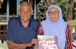 Abdulla Rafeeq and Aisaadhy hold up an old photograph of their families. PHOTO: HAWWA AMAANY ABDULLA / THE EDITION