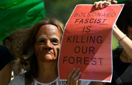A masked climate activist stands next to a fellow protester holding a sign against Brazilian President Jair Bolsonaro during a demonstration in Barcelona against Amazon fires on August 23, 2019. - Official figures show nearly 73,000 forest fires were recorded in Brazil in the first eight months of the year -- the highest number for any year since 2013. Most were in the Amazon. The extent of the area damaged by fires has yet to be determined, but smoke has choked Sao Paulo and several other Brazilian cities in the past week. (Photo by LLUIS GENE / AFP)