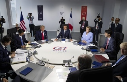 (From L) Italian Prime Minister Giuseppe Conte, Japanese Prime Minister Shinzo Abe, US President Donald Trump, French President Emmanuel Macron, German Chancellor Angela Merkel, Canadian Prime Minister Justin Trudeau, Britain's Prime Minister Boris Johnson attend a work session in the Casino of Biarritz on August 26, 2019, on the third and last day of the annual G7 Summit attended by the leaders of the world's seven richest democracies, Britain, Canada, France, Germany, Italy, Japan and the United States. (Photo by Ian LANGSDON / POOL / AFP)