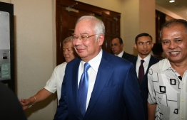 Malaysia's former prime minister Najib Razak (C) arrives at the High Court in Kuala Lumpur on August 28, 2019. (Photo by Mohd RASFAN / AFP)