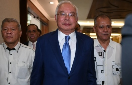 Malaysia's former prime minister Najib Razak (C) arrives for his trial at the High Court in Kuala Lumpur on August 28, 2019. - Malaysian ex-leader Najib Razak's most significant 1MDB trial begins on August 28, centring on allegations that hundreds of millions of dollars linked to the state fund ended up in his bank account. (Photo by Mohd RASFAN / AFP)