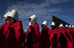 "(FILES) In this file photo taken on August 05, 2018 Activists in favour of the legalization of abortion disguised as characters from Canadian author Margaret Atwood's feminist dystopian novel ""The Handmaid's Tale"", perform at the ""Parque de la Memoria"" (Remembrance Park) in Buenos Aires. - Margaret Atwood released the much-anticipated sequel to her award-winning 1985 novel ""The Handmaid's Tale"" on Tuesday, with ""The Testaments"" set to become a similar smash. (Photo by ALEJANDRO PAGNI / AFP)"