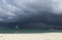 A woman walks on the beach as a storm approaches in Nassau, Bahamas, on September 12, 2019. - The National Oceanic and Atmospheric Administration (NOAA) reported a weather disturbance (95L) over the southeast and central Bahamas on September 12, 2019, which is growing better organized and is likely to form into a tropical depression or tropical storm by September 14. NOAA said the system is moving toward the northwest. If this trend continues Potential Tropical Cyclone advisories will likely be initiated later Thursday. This disturbance will bring heavy rainfall and gusty winds across portions of the Bahamas through Friday. (Photo by Andrew CABALLERO-REYNOLDS / AFP)