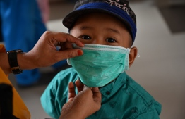 A young boy wears a mask to protect against air pollution. PHOTO: ADEK BERRY / AFP