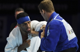 (FILES) In this file photo taken on August 28, 2019, Iran's Saeid Mollaei (in white) fights against Belgium's Matthias Casse during the semi-final of the men's under 81kg category during the 2019 Judo World Championships at the Nippon Budokan, a venue for the upcoming Tokyo 2020 Olympic Games, in Tokyo. - Iran was suspended from all  competitions, administrative and social activities origanized or authorised by International Judo Federation and its Unions for instructing Mollaei, one of its judokas, to intentionally withdraw during the last 2019 World Championship in Tokyo in order to avoid confronting an Israeli fighter, said the organisation. Iran and Israel are in a state of war and do not have diplomatic relations. (Photo by Charly TRIBALLEAU / AFP)
