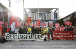 Activists of the non-governmental organization Campact demonstrate holding banners reading (From L) 'Berlin 4 future' and 'Groko climate package, that's not enough' during a protest action outside the Chancellery where a meeting on the climate protection takes place on September 19, 2019 in Berlin. (Photo by AXEL SCHMIDT / AFP)