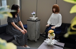 "This photo taken on June 16, 2019 shows an assistant (L) for robotician Hiroshi Ishiguro ""talking"" with a robot at the research centre in Osaka. - Set in 2019, cult 80s movie ""Blade Runner"" envisaged a neon-stained landscape of bionic ""replicants"" genetically engineered to look just like humans. So far that has failed to materialise, but at a secretive research institute in western Japan, wild-haired roboticist Hiroshi Ishiguro is fine-tuning technology that could blur the line between man and machine. (Photo by CHARLY TRIBALLEAU / AFP) /"