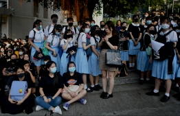 Schoolmates and protesters gather in support of form five student Tsang Chi-kin, 18, who was shot in the chest by police during violent pro-democracy protests that coincided with China's October 1 National Day, during a protest at a school in Hong Kong on October 2, 2019. - Hundreds of Hong Kongers staged a sit-in on October 2 outside the school of a protester who was shot by police as authorities said the wounded 18-year-old was now in a stable condition. (Photo by Mohd RASFAN / AFP)
