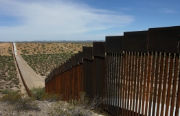 "(FILES) In this file photo taken on August 28, 2019 shows a portion of the wall on the US-Mexico border seen from Chihuahua State in Mexico, some 100 km from the city of Ciudad Juarez. - President Donald Trump on October 2, 2019 denied a US media report that he proposed extreme measures, including alligator-filled trenches, to stop migrants on the Mexican border. ""The press is trying to sell the fact that I wanted a Moot stuffed with alligators and snakes, with an electrified fence and sharp spikes on top, at our Southern Border,"" Trump tweeted, later correcting the spelling to read ""Moat.""""I may be tough on Border Security, but not that tough. The press has gone Crazy. Fake News!"" Trump wrote. (Photo by HERIKA MARTINEZ / AFP)"