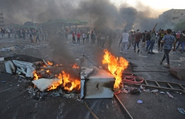 Iraqi protesters burn objects to block the road during clashes amidst demonstrations against state corruption, failing public services, and unemployment in the Iraqi capital Baghdad's central Tayeran Square on October 3, 2019. - Iraqi security forces fired live rounds early today to break up protests help for a third day in Baghdad, an AFP photographer said, despite a curfew in effect since dawn. (Photo by AHMAD AL-RUBAYE / AFP)