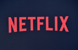 """(FILES) In this file photo taken on June 28, 2019 Netflix logo is seen on the backdrop of Netflix's """"Stranger Things 3"""" premiere at Santa Monica high school Barnum Hall in Santa Monica, California. - Netflix on October 3, 2019 said it was cooperating with a probe into whether it evaded taxes in Italy, even though it has no office or employees in that country. The crux of the matter appeared to be whether server units used to help handle the streaming load for the California-based firm were enough to designate it as having permanent status in Italy in the eyes of local tax collectors. (Photo by Chris Delmas / AFP)"""