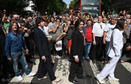 """(FILES) In this file photo taken on August 08, 2019 Beatles lookalike band 'Fab Gear' and fans of The Beatles pose at the famous Abbey Road zebra crossing in London, England, the 50th anniversary of the day that the iconic Beatles album cover photograph was taken. - Classic Beatles album """"Abbey Road"""" is back at number one in Britain half a century after its first release, with the band breaking their own record for the longest gap between stints at the top of the charts. (Photo by Daniel LEAL-OLIVAS / AFP)"""