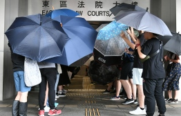 Protesters cover themselves with umbrellas as they gather outside the Eastern District Courts in Hong Kong on October 7, 2019, where the first protesters arrested for wearing face masks appeared in court. - Hong Kong protesters arrested for defying a new face mask ban appeared in court on October 7 following a violent weekend of unrest which saw bloody clashes with police and widespread vandalism that crippled the city's train network. (Photo by Mohd RASFAN / AFP)