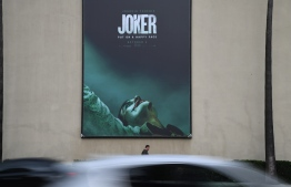 """A poster for the upcoming film """"The Joker"""" is seen outside Warner Brothers Studios in Burbank, California, September 27, 2019. - The Los Angeles Police Department said Friday it plans to step up its visibility around movie theaters for the opening of """"Joker"""" because of heightened fears over the film's content. (Photo by Robyn Beck / AFP)"""