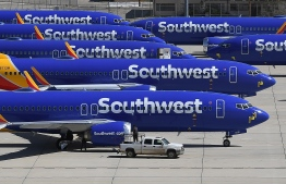 """(FILES) In this file photo taken on March 28, 2019 Southwest Airlines Boeing 737 MAX aircraft are parked on the tarmac after being grounded, at the Southern California Logistics Airport in Victorville, California. - Pilots from Texas-based Southwest Airlines said October 7, 2019, they had filed a lawsuit against Boeing, accusing it of """"deliberately misleading"""" them over the 737 MAX, which has been grounded after two deadly crashes. (Photo by Mark RALSTON / AFP)"""