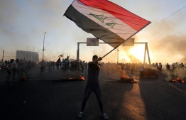 An Iraqi protester waves the national flag during a demonstration against state corruption, failing public services, and unemployment, in the Iraqi capital Baghdad on October 5, 2019. - Renewed protests took place under live fire in Iraq's capital and the country's south Saturday as the government struggled to agree a response to days of rallies that have left nearly 100 dead. The largely spontaneous gatherings of demonstrators -- whose demands have evolved since they began on Tuesday from employment and better services to fundamental government change -- have swelled despite an internet blackout and overtures by the country's elite. Hours after a curfew in Baghdad was lifted on Saturday morning, dozens of protesters rallied around the oil ministry in the capital, facing live rounds fired in their direction, an AFP photographer said. (Photo by AHMAD AL-RUBAYE / AFP)