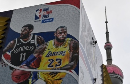 """A worker removes a promotional banner from a building for the National Basketball Association (NBA) October 10 preseason game in China between the Brooklyn Nets and the Los Angeles Lakers in Shanghai on October 9, 2019. - Chinese state media slammed the NBA for an """"about-face"""" on October 9 after the body said it would not apologise for a tweet by the Houston Rockets General Manager supporting pro-democracy protests in Hong Kong. (Photo by HECTOR RETAMAL / AFP)"""