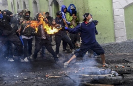 Demonstrators clash with riot police in Quito on October 9, 2019 on the second day of violent protests over a fuel price hike ordered by the government to secure an IMF loan. - The violence broke out as thousands of people representing indigenous groups, farmers and labour unions marched on a square in downtown Quito near the government headquarters demanding that Moreno reinstate fuel subsidies. (Photo by Martin BERNETTI / AFP)