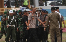 """Indonesian police and military carry Indonesia's Security Minister Wiranto (C) to a helicopter to be medevaced after he was stabbed in Pandeglang, Banten province, on October 10, 2019. - Indonesia's chief security minister Wiranto suffered """"two deep wounds"""" in his stomach after he was stabbed by a suspected militant on October 10, 2019, according to police and a hospital spokesman, adding that a local police chief was also injured. (Photo by SAMMY / AFP)"""