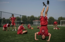 (FILES) In a file photo taken on September 22, 2016 students stretch following an under-14 training session at the Pyongyang International Football School in Pyongyang. - North and South Korea face each other in a World Cup qualifier on October 15, 2019 for their first ever competitive men's match in Pyongyang, while talks on the North's nuclear arsenal remain deadlocked. (Photo by Ed JONES / AFP) / TO GO WITH AFP STORY NKOREA-SKOREA-DIPLOMACY-FBL-KOR-PRK,ADVANCER BY SUNGHEE HWANG