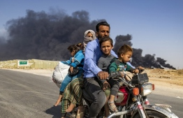 "Displaced people, fleeing from the countryside of the Syrian Kurdish town of Ras al-Ain along the border with Turkey, ride a motorcycle together along a road on the outskirts of the nearby town of Tal Tamr on October 16, 2019 as they flee from the Turkish ""Peace Spring"" military operation, with smoke plumes of tire fires billowing in the background to decrease visibility for Turkish warplanes in the area. (Photo by Delil SOULEIMAN / AFP)"