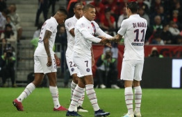 """Paris Saint-Germain's French forward Kylian Mbappe (C) is congratulated by Paris Saint-Germain's Argentine midfielder Angel Di Maria (R) after scoring a goal during the French L1 football match between OGC Nice (OGCN) and Paris Saint-Germain (PSG) at """"Allianz Riviera"""" stadium in Nice, southern France, on October 18, 2019. (Photo by Valery HACHE / AFP)"""