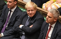 """A handout picture released by the UK Parliament shows Britain's Prime Minister Boris Johnson (C) smiling in the House of Commons in London on October 19, 2019, during a debate on the Brexit deal. - A day of high drama in parliament on Saturday saw lawmakers vote for a last-minute amendment to the deal that could force the government to seek to extend the October 31 deadline to leave. (Photo by JESSICA TAYLOR / UK PARLIAMENT / AFP) / RESTRICTED TO EDITORIAL USE - MANDATORY CREDIT """" AFP PHOTO / UK PARLIAMENT / JESSICA TAYLOR  """" - NO USE FOR ENTERTAINMENT, SATIRICAL, MARKETING OR ADVERTISING CAMPAIGNS - EDITORS NOTE THE IMAGE HAS BEEN DIGITALLY ALTERED AT SOURCE TO OBSCURE VISIBLE DOCUMENTS /"""