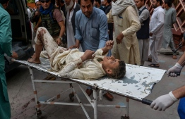 "Volunteers carry an injured man on a stretcher to a hospital, following a bomb blast in Haska Mina district of Nangarhar Province on October 18, 2019. - At least 62 people were killed by a blast inside an Afghan mosque during Friday prayers on October 18, according to officials, a day after the United Nations said violence in the country had reached ""unacceptable"" levels. (Photo by NOORULLAH SHIRZADA / AFP)"