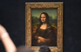 "(FILES) In this file photograph taken on October 7, 2019, visitors take photographs in front of The Mona Lisa (La Gioconda) after it was returned to its place at the Louvre Museum in Paris. - The Louvre in Paris is putting the finishing touches to an ambitious Leonardo da Vinci retrospective opening on October 24, 2019, which groups more than 160 of the artist's works and has already attracted close to 200,000 advance visitor bookings. Timed to coincide with the 500th anniversary of the famed artist's death, the show, simply called ""Leonardo da Vinci"", took a decade to put together and includes works on loan from Queen Elizabeth and Bill Gates. (Photo by ERIC FEFERBERG / AFP) /"