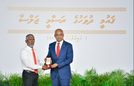 A family member accepts the National Award of Honour conferred posthumously on the late Dr Abdul Majeed Abdul Bari, for his contributions in the field of Islamic knowledge and education. PHOTO: HUSSAIN WAHEED / MIHAARU