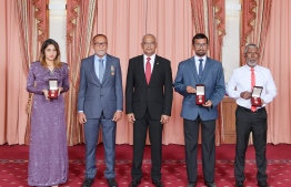 Family members of the late Dr Abdul Majeed Abdul Bari (R), the late Dr Afrasheem Ali (R-2), and the late Sayyid Hassan (L), who were conferred the National Award of Honour posthumously, pose for a photograph with President Ibrahim Mohamed Solih (C) after the ceremony held to mark the National Day on October 28, 2019, at Dharubaaruge. PHOTO/PRESIDENT'S OFFICE