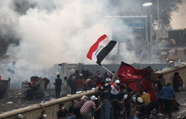 Iraqi anti-government protesters take cover from security forces firing tear gas to keep demonstrators from storming the Green Zone, which hosts government offices and foreign offices, on October 28, 2019 in Baghdad. - The Iraqi army announced it would impose an overnight curfew in the capital as students and schoolchildren joined spreading protests to demand an overhaul of the government. Swathes of Iraq have been engulfed by demonstrations over unemployment and corruption this month that have evolved into demands for regime change. (Photo by - / AFP)