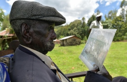 Kibore Cheruiyot Ngasura, 95, sits in his compound with an old picture, bearing bearing his image and those of some of of his clansmen with whom he was forcefully evicted from their lands, at his farm in in Tugunon village, Kipkelion in Kenya's Kericho highlands, Kericho county,on October 8, 2019. - Kericho hosts vast tea estates established at the turn of the 20th century by British settlers who are said to have appropriated the ancestral lands of the local Kipsigis and Tulai communities to start the plantations, displacing thousands of the natives whose decsendants today are demanding a return of their lands currently under tea estates, large swathes of which are still held under colonial-era titles by organisations based in the United-Kingdom. Kibore is among those that were forcefully  evicted from their lands, originally at Kimigik village in Ainamoi in 1934 and deported to an island on Lake Victoria. (Photo by TONY KARUMBA / AFP)