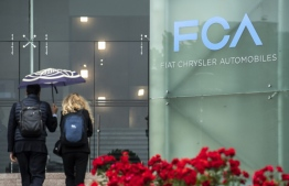(FILES) In this file photo taken on May 27, 2019 people walk past the logo of Fiat Chrysler Automobiles (FCA) at the Fiat Mirafiori car plant in Turin, northern Italy. Fiat Chrysler, Peugeot discuss merger to create $50 bn entity. MARCO BERTORELLO / AFP