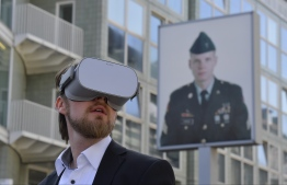 (FILES) In this file photo taken on August 22, 2019 Jonas Rothe, founder and CEO of Timeride, a company offering Virtual Reality tours through a still-divided Berlin, poses next to Checkpoint Charlie on August 22, 2019 in Berlin. (Photo by Tobias SCHWARZ / AFP)