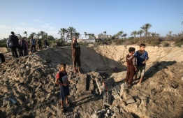 Palestinian children stand around a crater caused by an Israeli airstrike launched in response to rocket fire, in Khan Yunis in the southern Gaza Strip on November 2, 2019. - Dozens of strikes hit the Palestinian enclave in the early hours today, targeting bases of the strip's Islamist rulers and allied groups, a security source in Gaza said. (Photo by SAID KHATIB / AFP)
