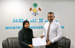 Higher Education Minister Dr Ibrahim Hassan handing over scholarship funds to the guardian of a student. PHOTO: MINISTRY OF HIGHER EDUCATION