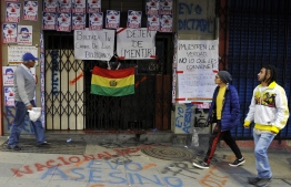 """People walk past at the closed entrance of the state TV channel BoliviaTV with pictures depicting Bolivian President Evo Morales as a clown reading """"Fraud"""" and signs reading """"Stop lying"""" and """"Show the truth and not what is convenient to you"""", after a protest on November 9, 2019, in La Paz. - Police in three Bolivian cities joined anti-government protests Friday, in one case marching with demonstrators in La Paz, in the first sign security forces are withdrawing support from President Evo Morales after a disputed election that has triggered riots. (Photo by JORGE BERNAL / AFP)"""
