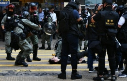 A man (C, bottom) is detained by police during a protest in Hong Kong's Central district on November 11, 2019. - A Hong Kong policeman shot a masked protester in the torso on November 11 morning, igniting clashes across the city and renewed fury towards the force as crowds took to the streets to block roads and hurl insults at officers. (Photo by Anthony WALLACE / AFP)