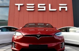 """(FILES) In this file photo taken on October 23, 2019 cars and a logo are pictured at the showroom and service center for the US automotive and energy company Tesla in Amsterdam. - Tesla CEO Elon Musk announced on November 12, 2019 in Berlin the construction of a new """"gigafactory"""" in the outskirts of the German Capital city. (Photo by John THYS / AFP)"""