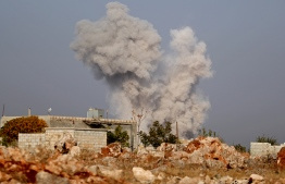Smoke billows following airstrikes by pro-government forces on the village of Kafr Nabl, in Syria's southern Idlib province on November 13, 2019. (Photo by Omar HAJ KADOUR / AFP)