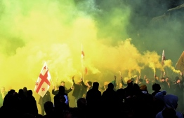 """Georgian opposition supporters wave Georgian flags amidst smoke from coloured flares as they protest outside the parliament in central Tbilisi on November 17, 2019, to demand the government's resignation and early parliamentary polls. - In the biggest anti-government rally in years, protesters demonstrated outside the parliament building on the capital Tbilisi's main thoroughfare. AFP journalists estimated the crowd at more than 20,000. Demanding the government's resignation and snap parliamentary polls, the crowd waved Georgian and European Union flags, lit coloured flares and held up a giant banner with the anti-Ivanishvili slogan """"All Against One"""". (Photo by Vano Shlamov / AFP)"""