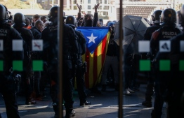 """Police officers and Catalan regional police 'Mossos D'Esquadra' officers stand guard at the entrance of the Barcelona Sants railway station, as demonstrators gather with a Catalan pro-independence """"Estelada"""" flag during a protest called by local Republic Defence Committees (CDR) on November 16, 2019 in Barcelona. (Photo by Pau Barrena / AFP)"""
